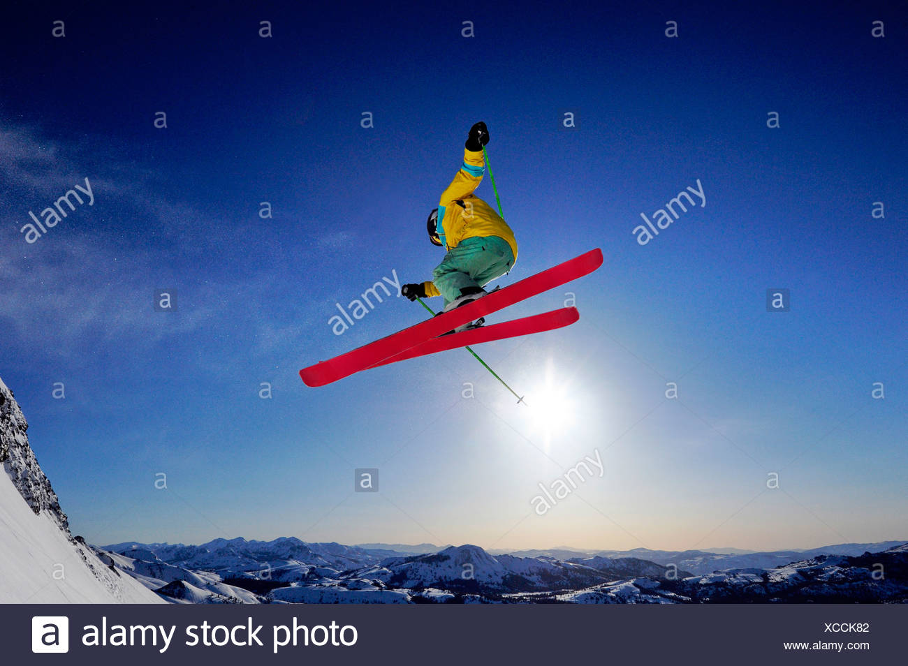 A skier soars through the air at sunrise in the Sierra Nevada mountains near Lake Tahoe, California. - Stock Image