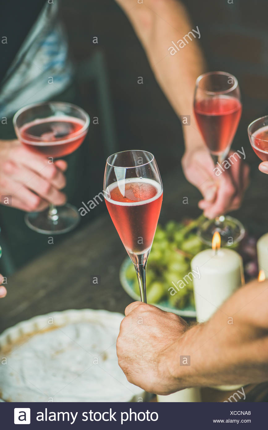 Holiday celebration table setting with food. Friends hands eating and drinking together. People having party, gathering, celebrating with rose champai - Stock Image