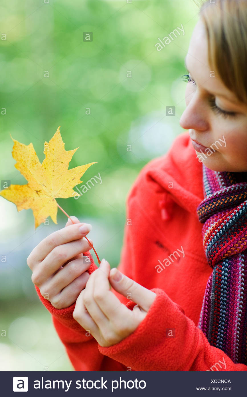 Portrait of a woman holding a maple leaf Sweden. - Stock Image