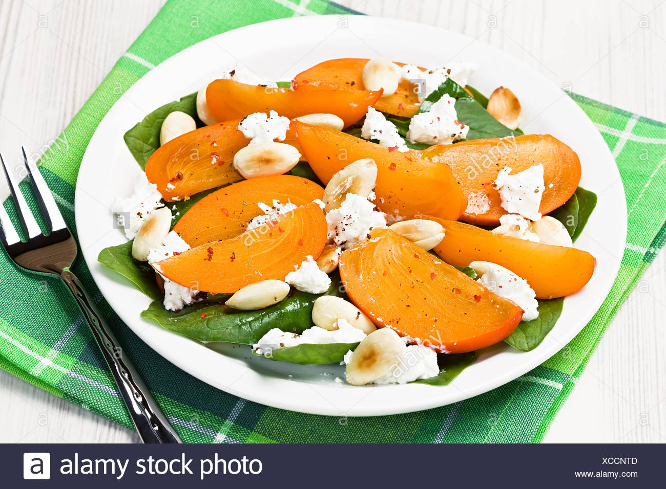 Spinach persimmon goat cheese salad with almonds - Stock Image