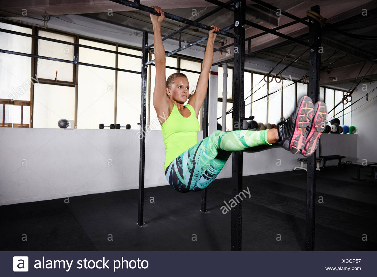 Young woman training on parallel bars in gym - Stock Image