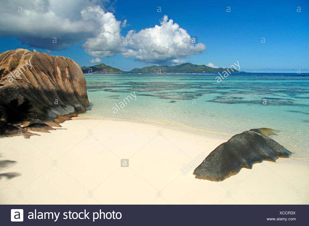 beach with granite rocks and view onto the island Praslin in the background, Seychelles, La Digue, Anse Source d Argent - Stock Image