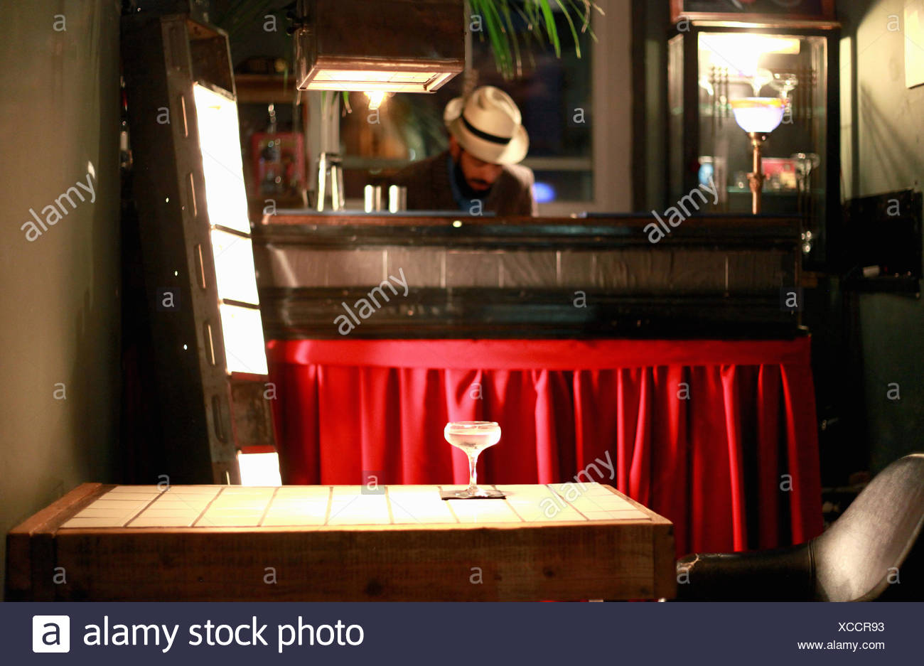 Cocktail on table, bartender behind counter at bar - Stock Image