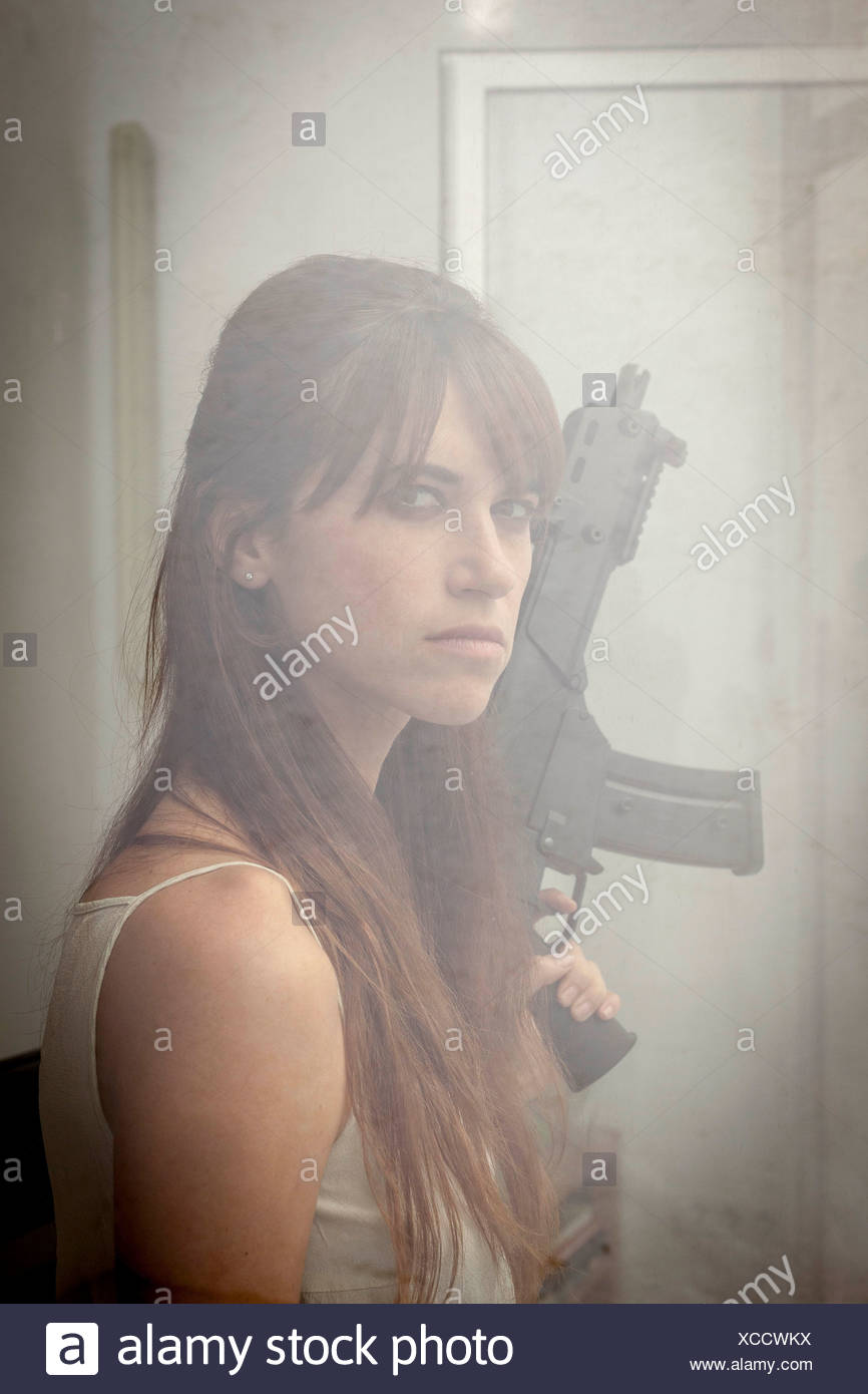 Woman holding machine gun at window Stock Photo
