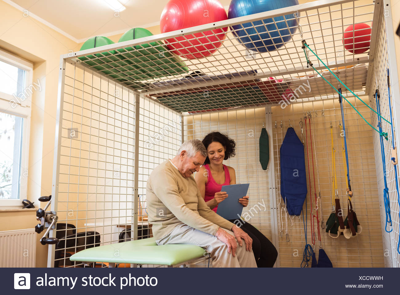 Female therapist discussing fitness report with senior man - Stock Image