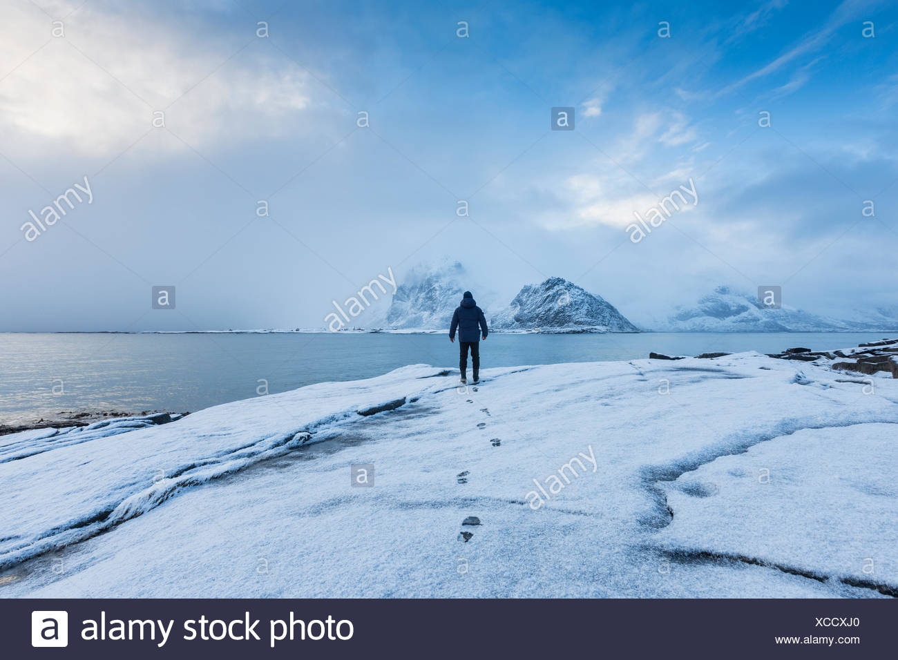 A man standing in snow looking out to sea - Stock Image