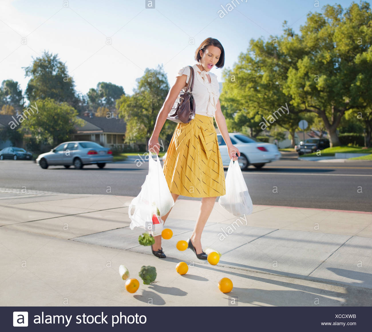 Woman dropping groceries on sidewalk - Stock Image