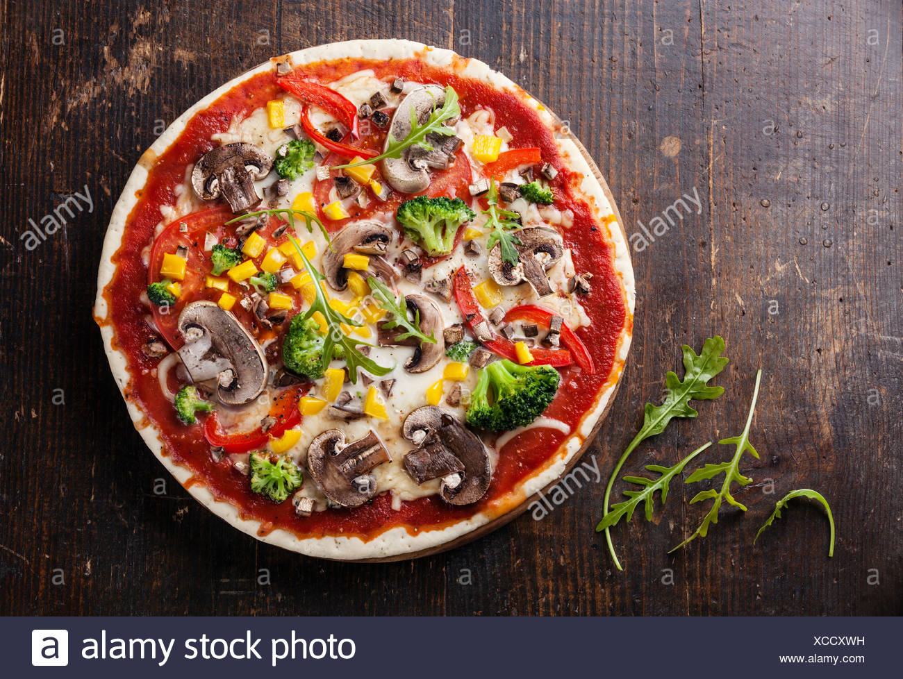 Vegetarian pizza with mushrooms and ruccola on wooden table - Stock Image