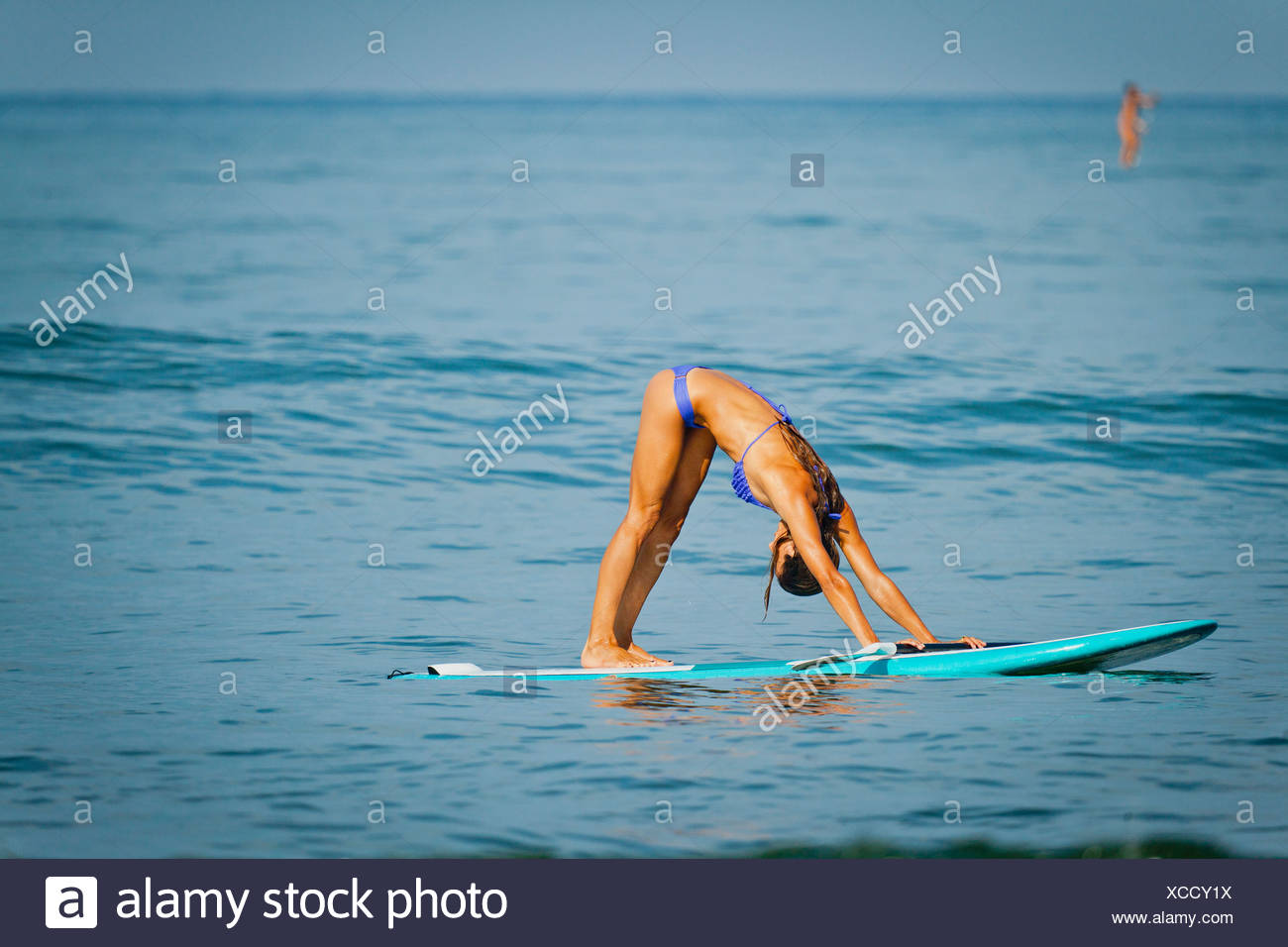 Woman In Yoga Pose On Paddle Board Stock Photo 283026406