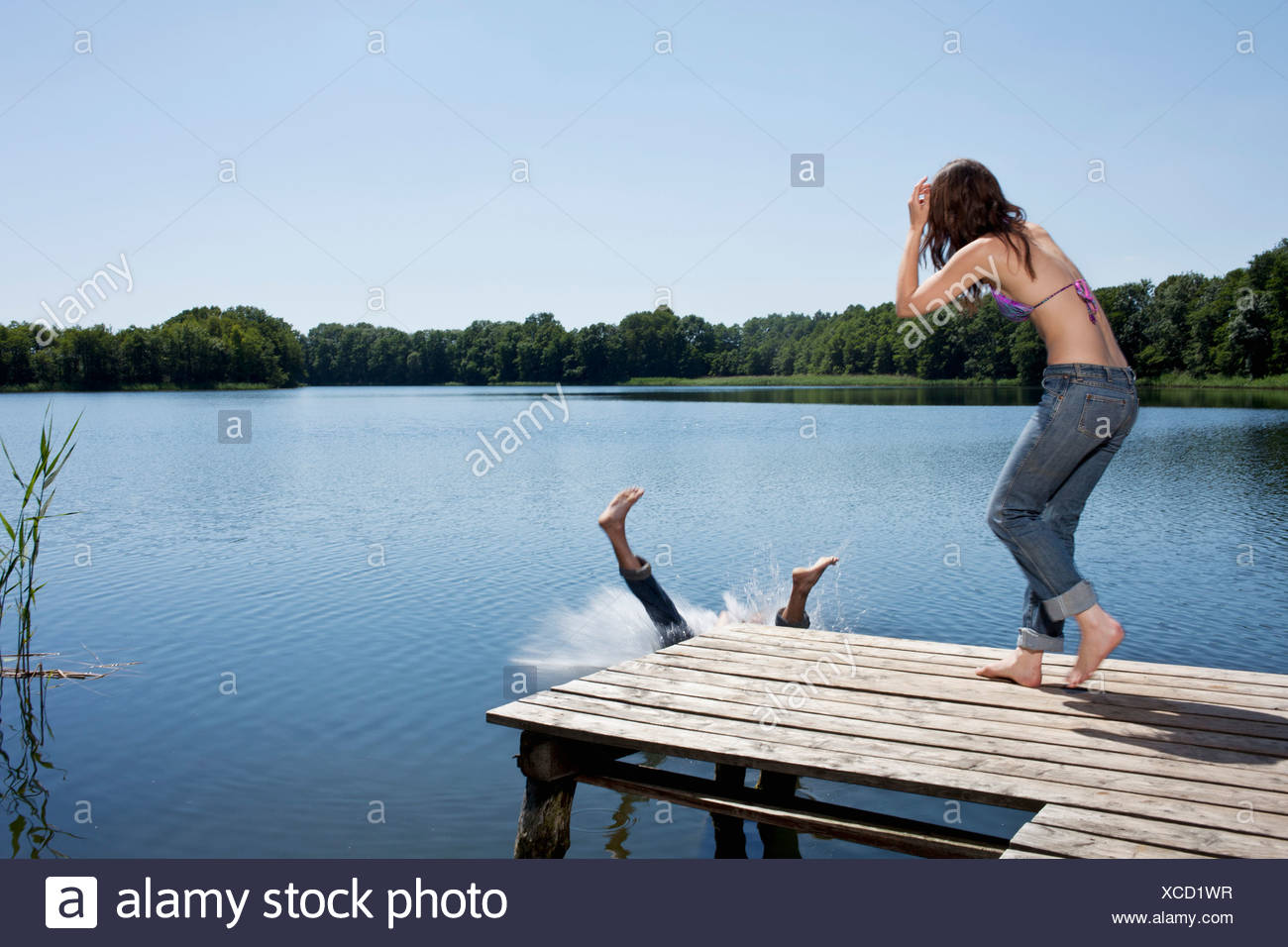 Guy splashes into water from jetty as girl watches - Stock Image