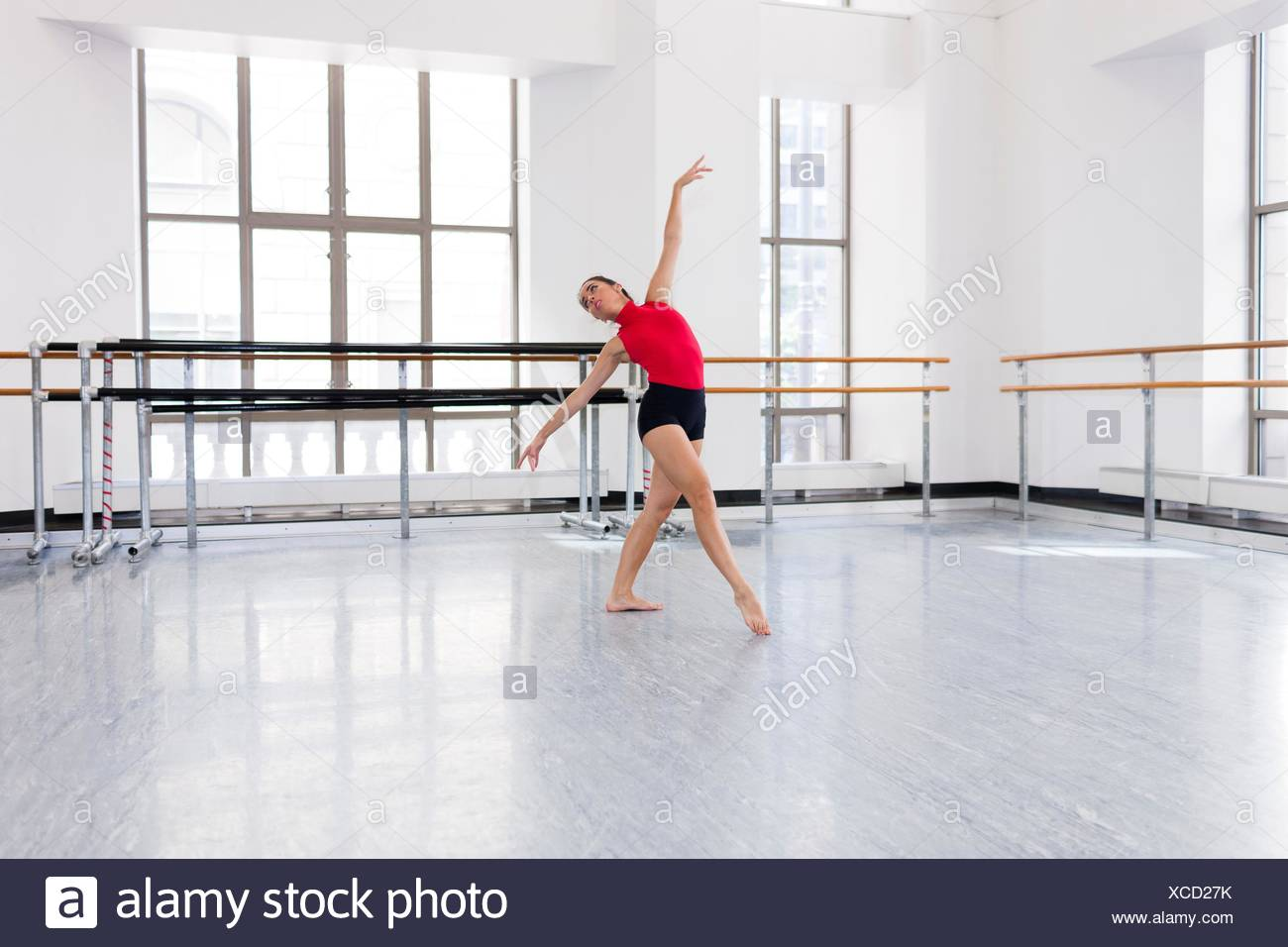 Young woman in dance studio dancing, head back, arms raised - Stock Image