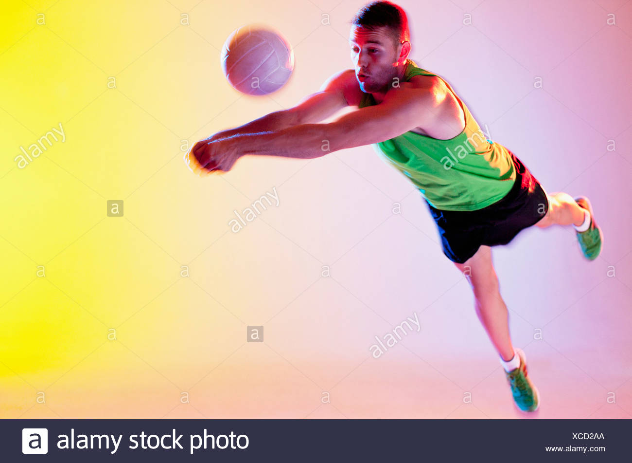 Volleyball player spiking ball - Stock Image