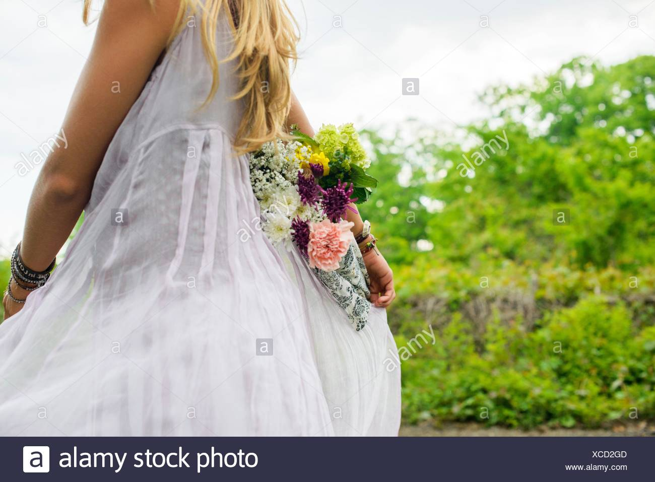 Cropped shot of young woman wearing white dress carrying bunch of flowers behind her back - Stock Image