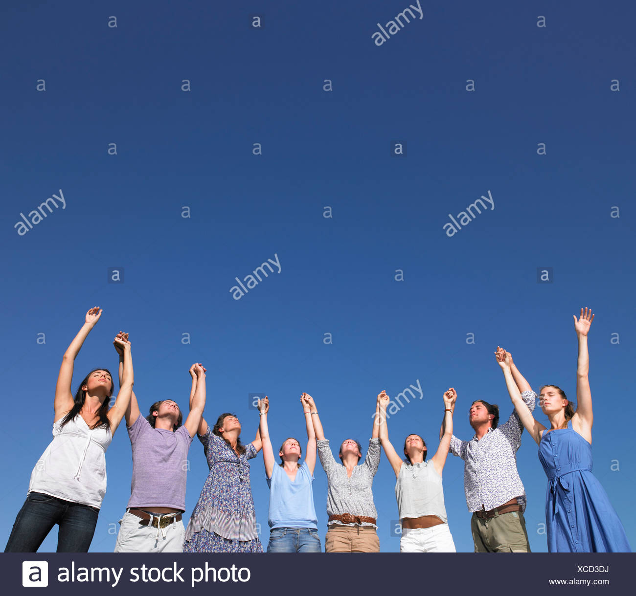 group of young people raising arms - Stock Image