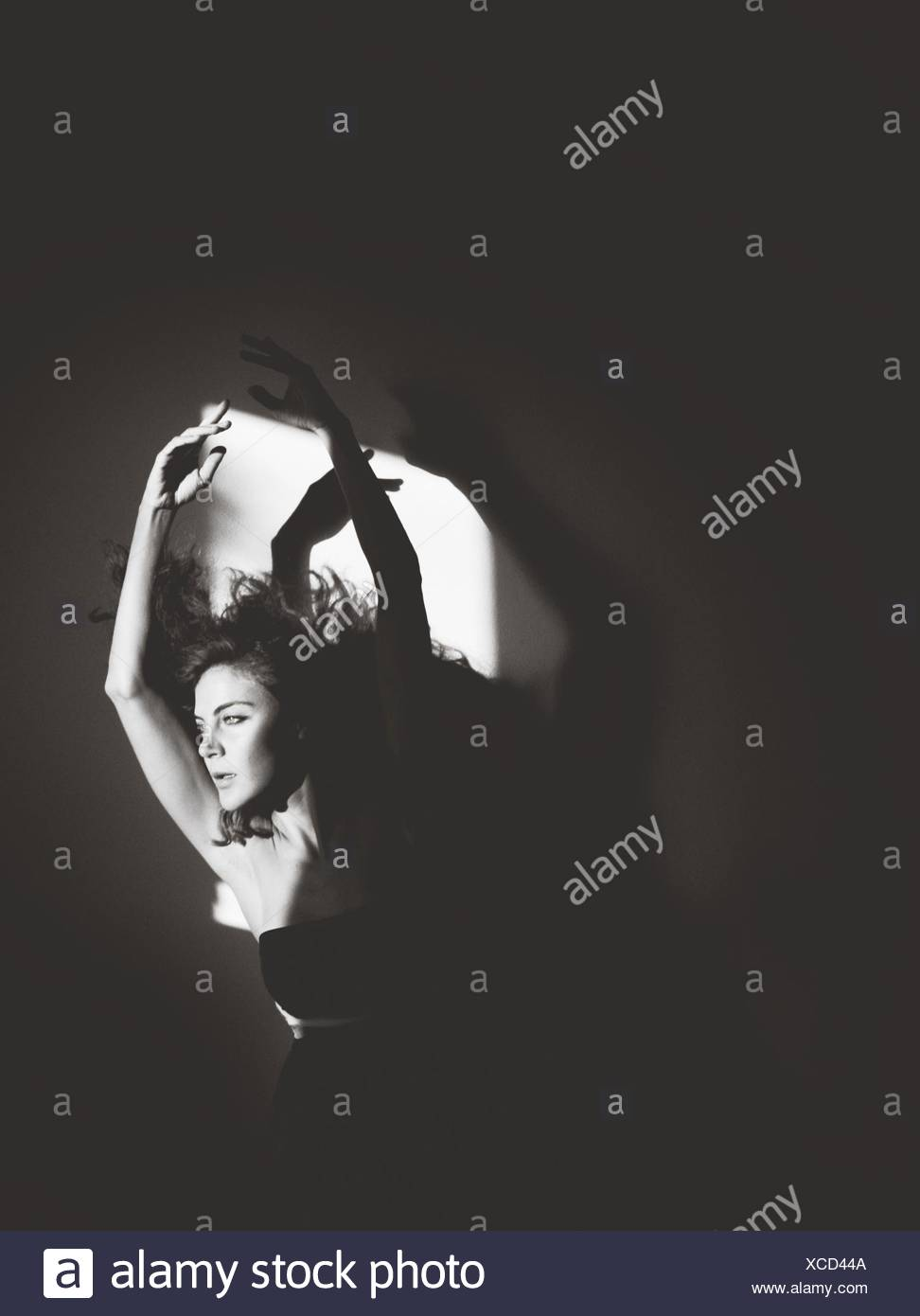 Portrait Of Young Woman With Arms Raised - Stock Image