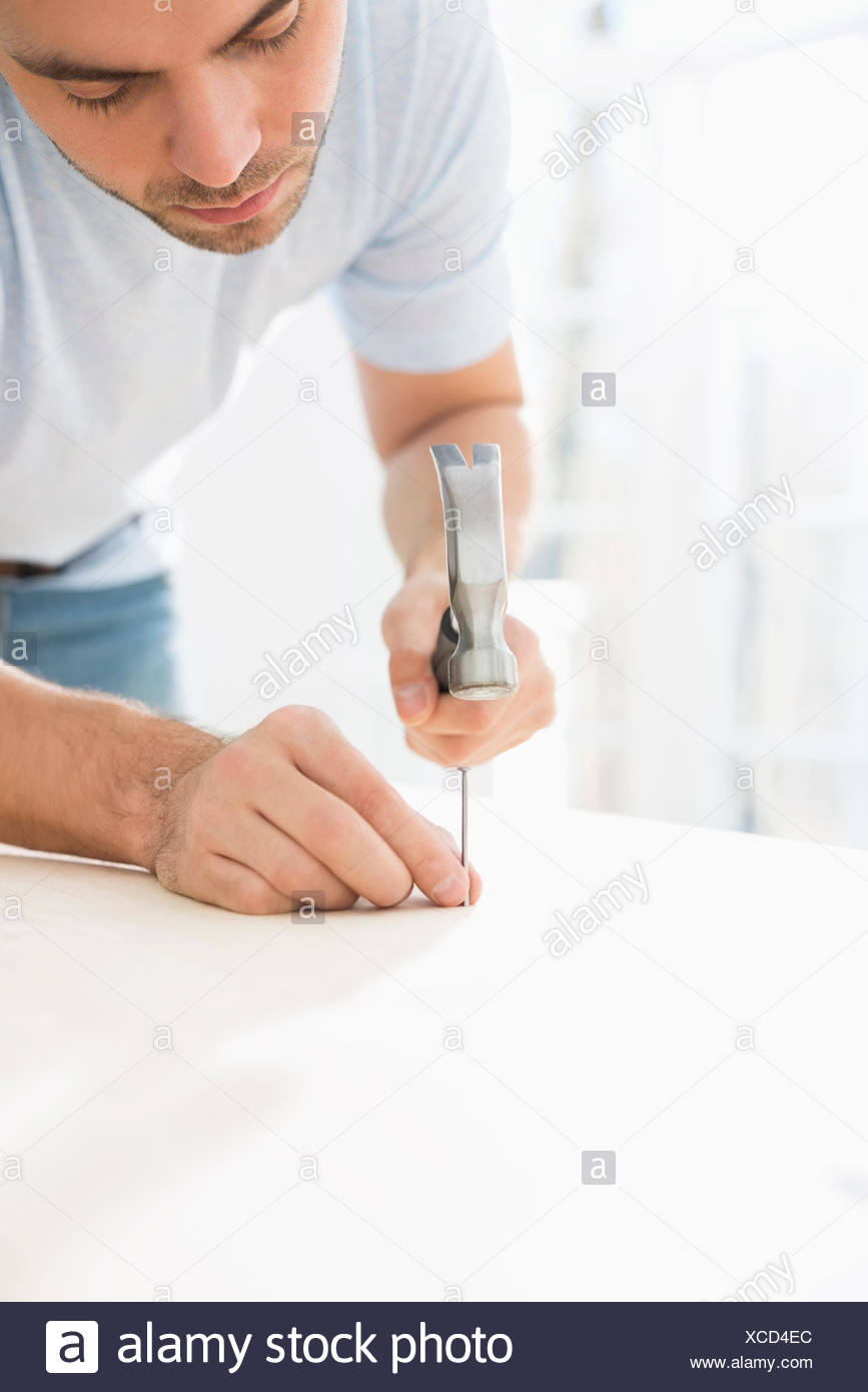 Mid-adult man nailing in table - Stock Image