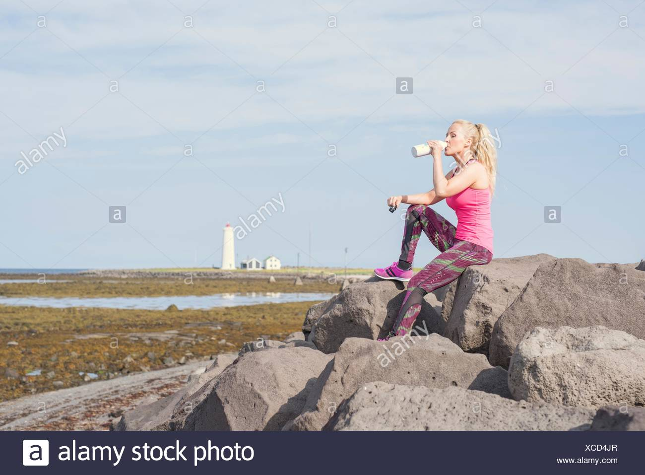 Female runner drinking from water bottle at coast - Stock Image
