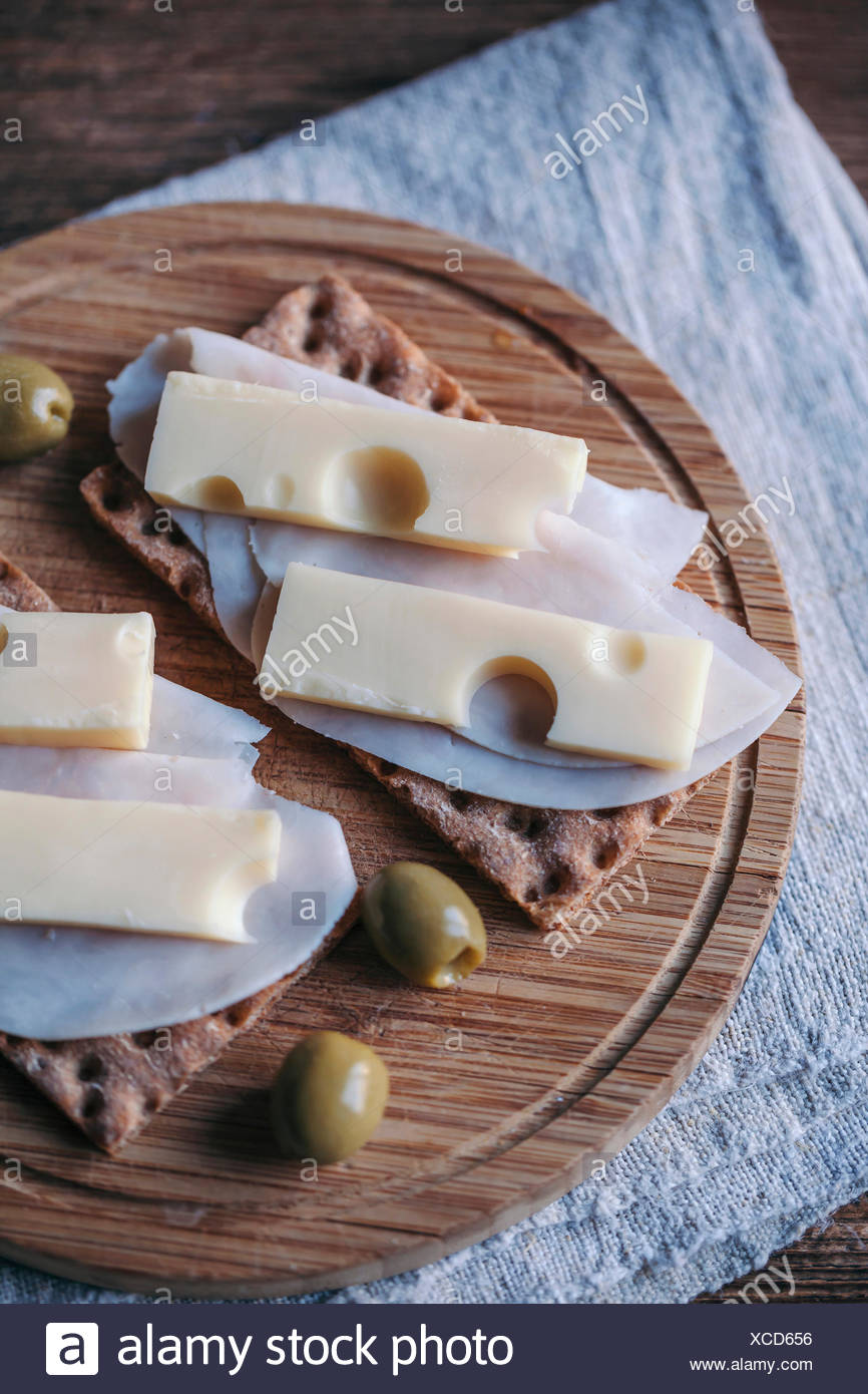Ham and cheese crisp bread sandwiches and olives served on a wooden cutting board Stock Photo