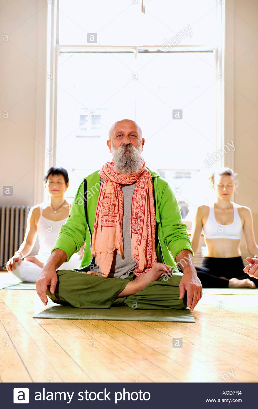 Mature man in lotus pose in yoga class - Stock Image