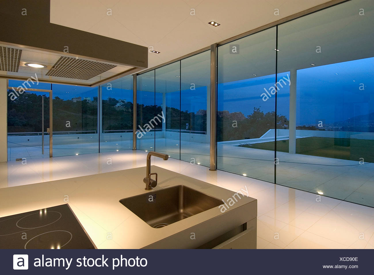 Sink In Island Unit In Modern Spanish Kitchen With Glass Walls And View Of Terrace At Night Stock Photo Alamy