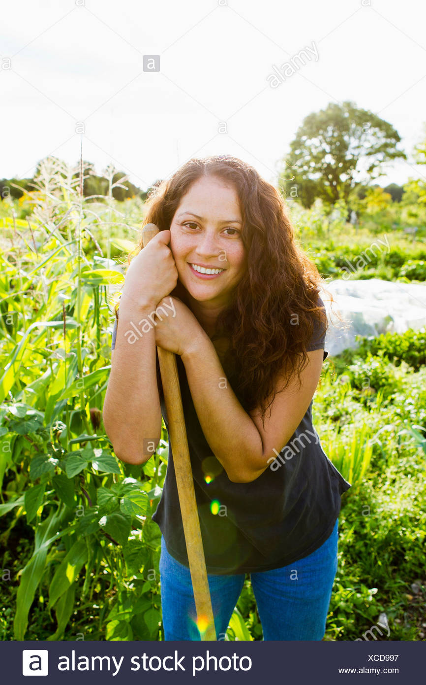 Portrait of young woman leaning on garden tool in allotment - Stock Image