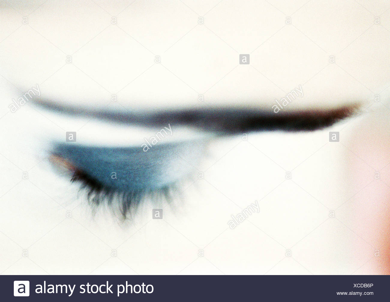 Woman's closed eye with blue eye shadow, close-up, high angle view, blurry. - Stock Image