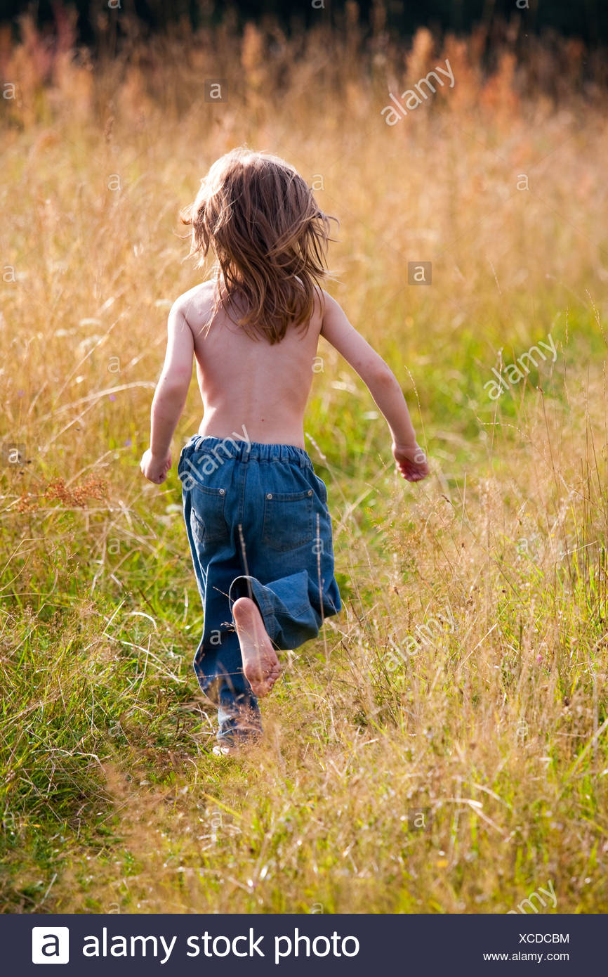 A child running along a path in the field - Stock Image