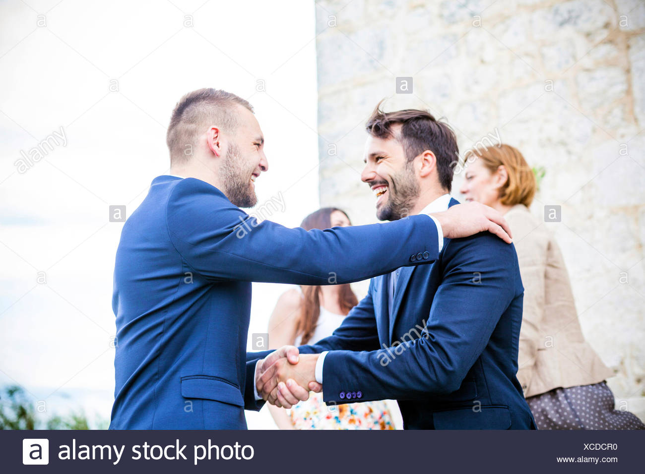 Bridegroom shaking hands with friend - Stock Image