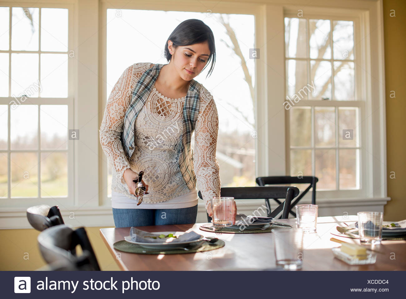A woman setting the table for a meal. - Stock Image