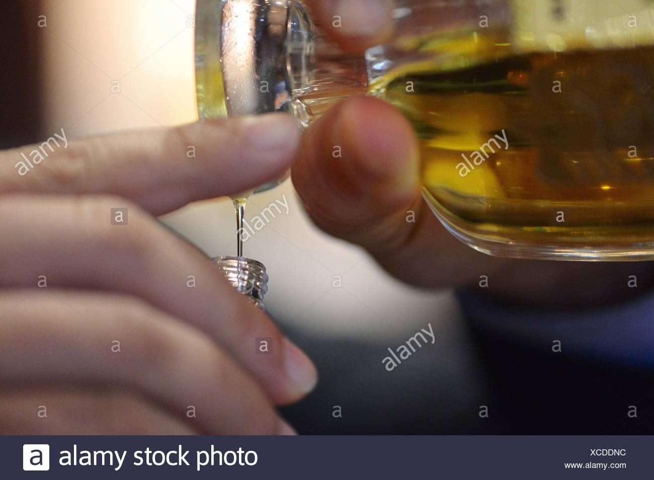 Cropped Image Of Hand Pouring Perfume In Bottle - Stock Image