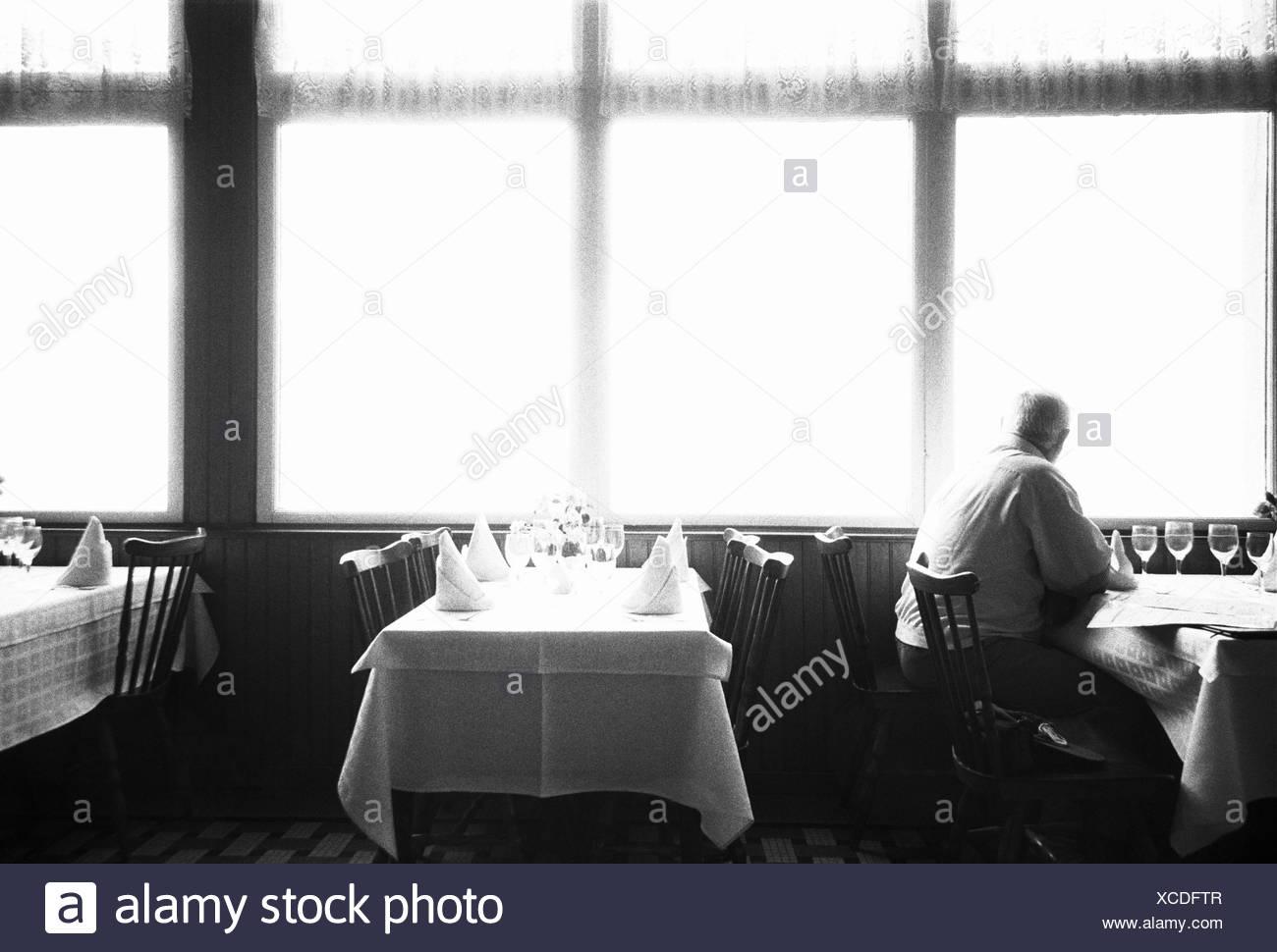 Restaurant, Gast, Blick, Fenster, s/w,  no model release  Cafe, Lokal, innen, Fensterplatz, Fensterfront, Tische, gedeckt, Mann, alt, Senior, Senioren, Alter, allein, einsam, Isolation, Einsamkeit, Ausblick, Einzelgänger, Resignation, Vereinsamung, Ti4 - Stock Image