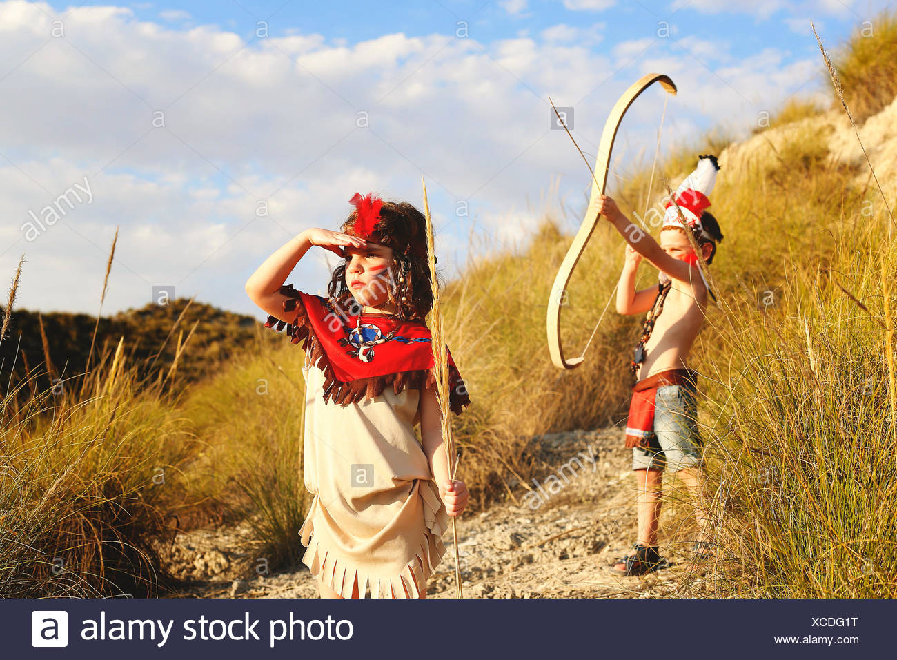 Boy and girl playing dressed up as Indians - Stock Image