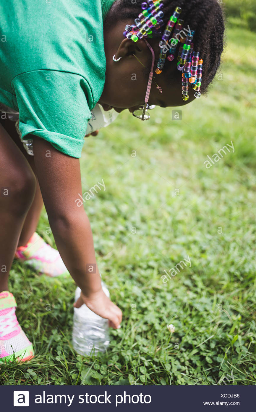 Girl picking up rubbish in parkland eco camp - Stock Image