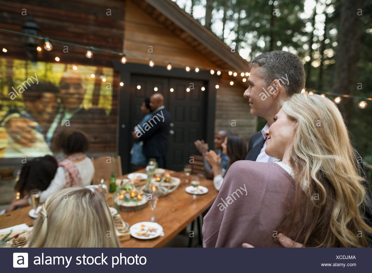 Affectionate couple watching projected slideshow at anniversary party on cabin balcony - Stock Image