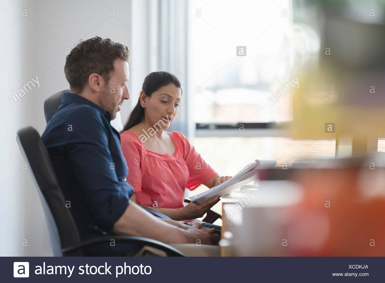Colleagues in discussion at office desk - Stock Image