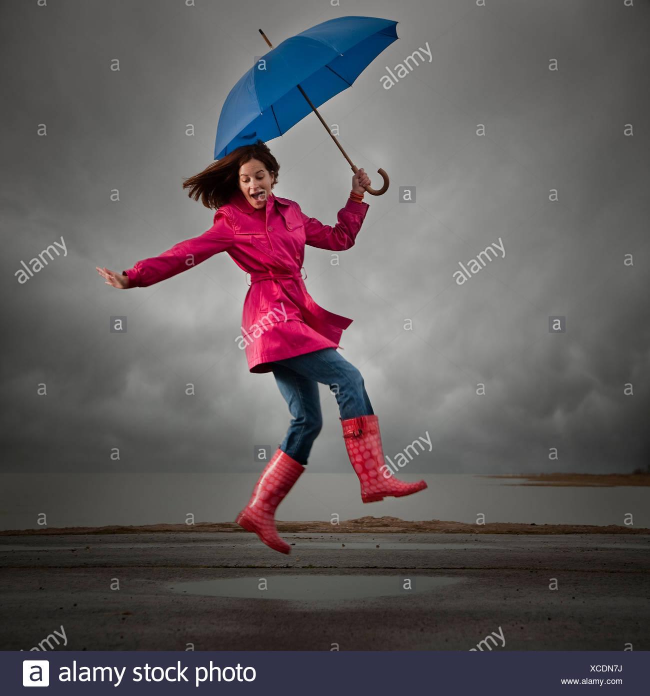 USA, Utah, Orem, woman with umbrella jumping under overcast sky - Stock Image