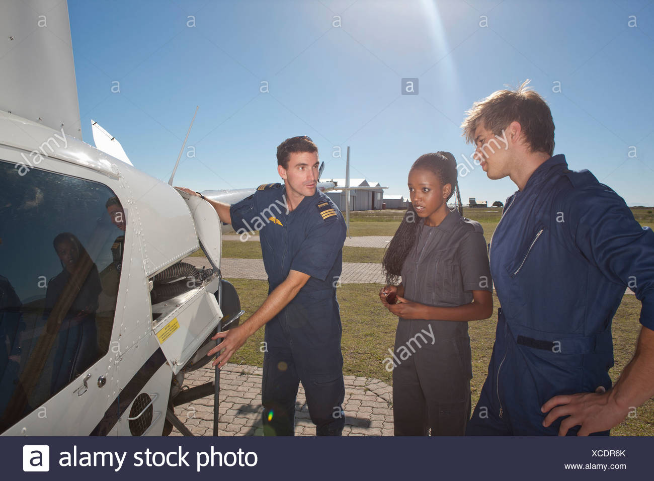 Flight instructor showing student pilots engine of helicopter - Stock Image