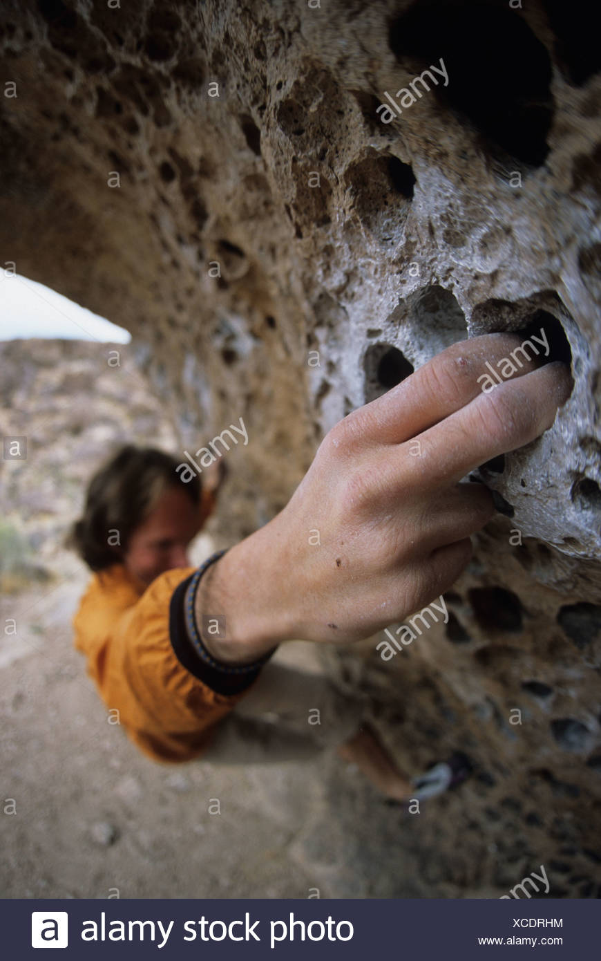 A climbers gripping on to the nice finger pockets on Hand to Hand Combat, v7, Happy Boulders, Bishops, California, United States - Stock Image