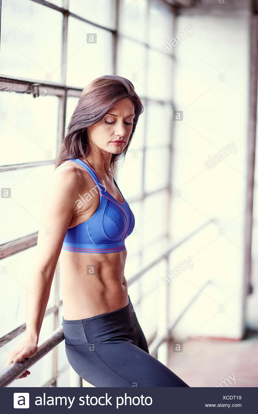 Portrait of muscular woman wearing crop top next to window - Stock Image