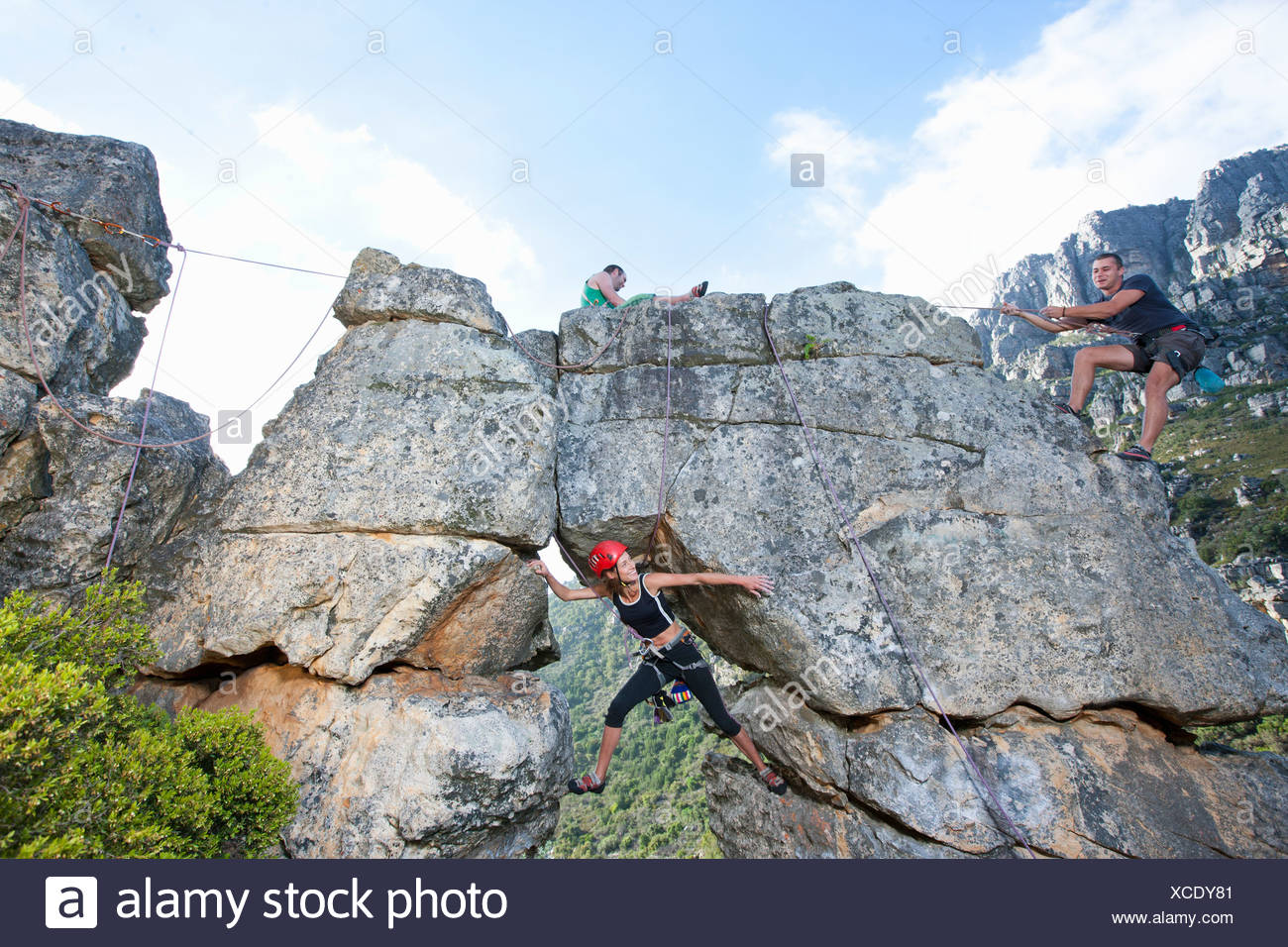 Three rock climbers climbing up rock formation - Stock Image