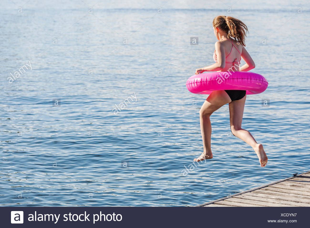 Girl jumping off a dock by Balsam Lake wearing inflatable ring; Ontario, Canada Stock Photo