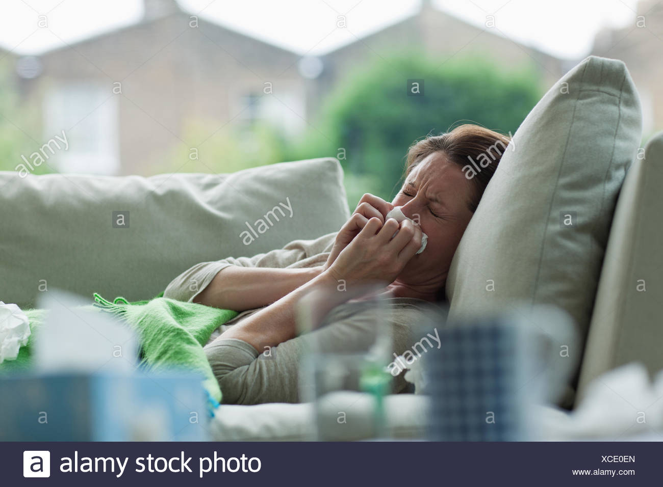 Sick woman laying on sofa blowing nose - Stock Image