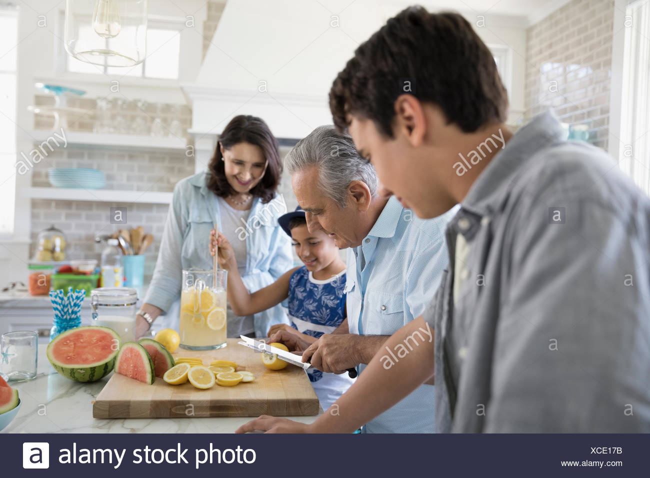 Multi-generation family making lemonade in kitchen - Stock Image