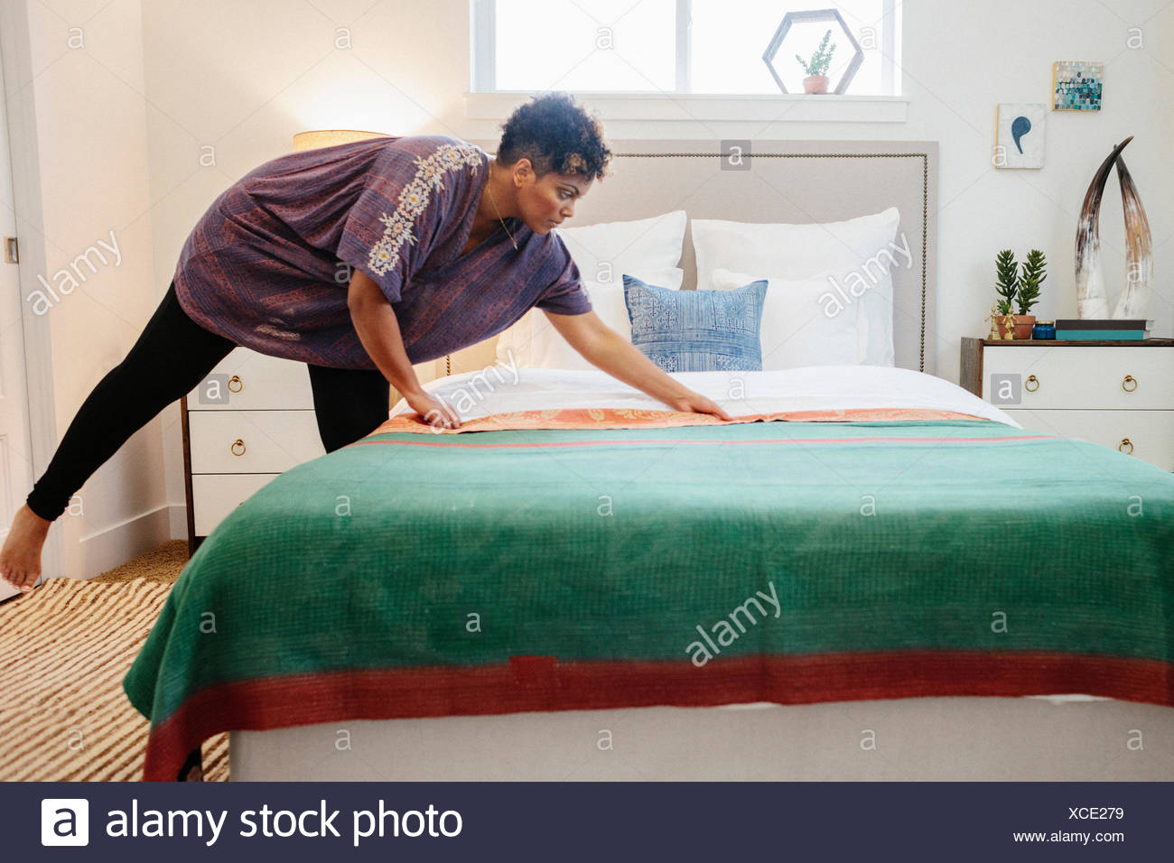 A woman smoothing a green fabric quilt  with red trim over a double bed in a light airy apartment - Stock Image