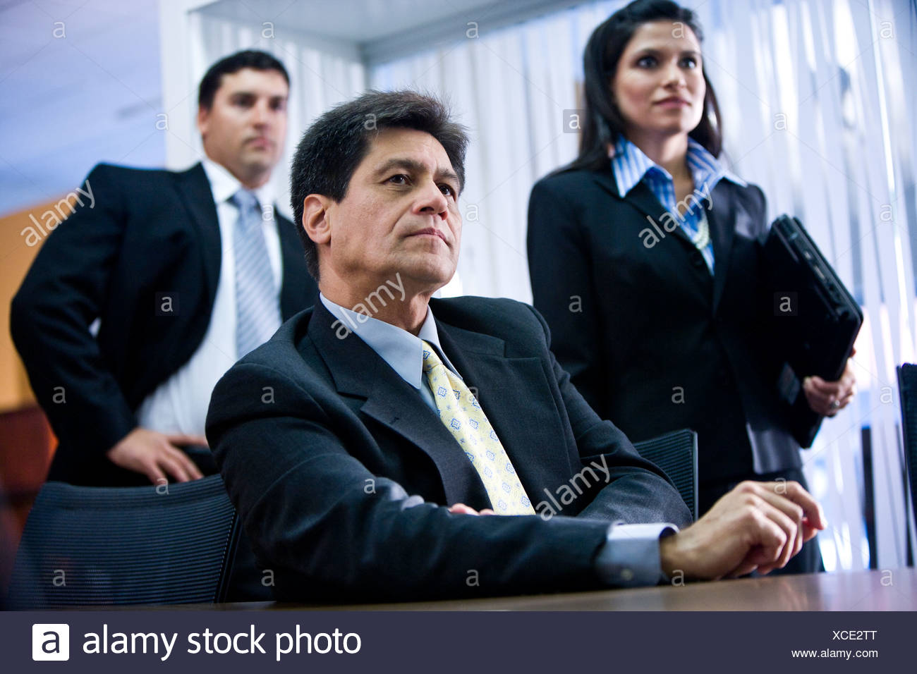 Hispanic businessman in meeting with younger colleagues behind Stock Photo
