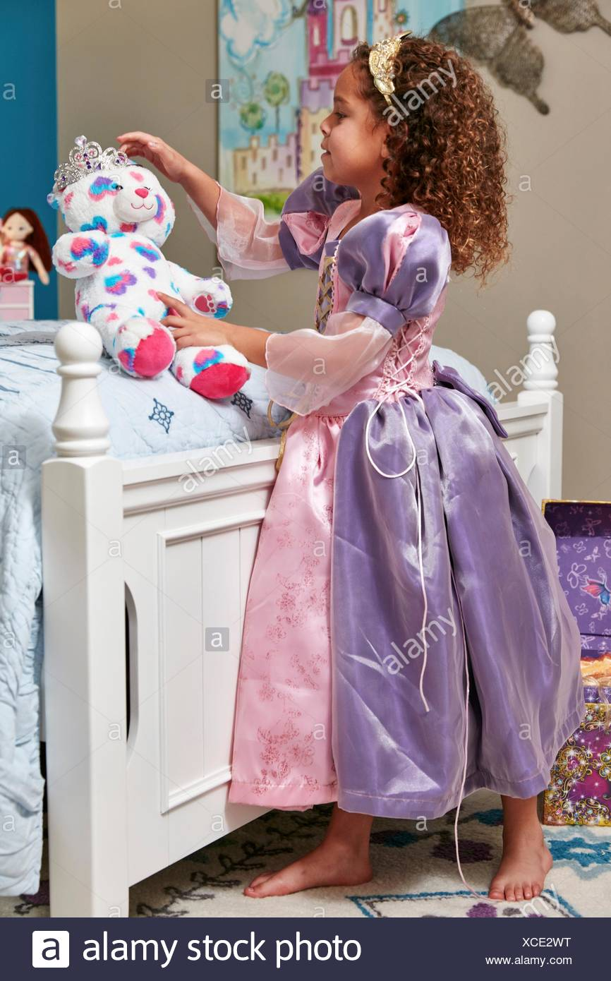 Side view of girl dressed up as princess play acting with teddy bear - Stock Image