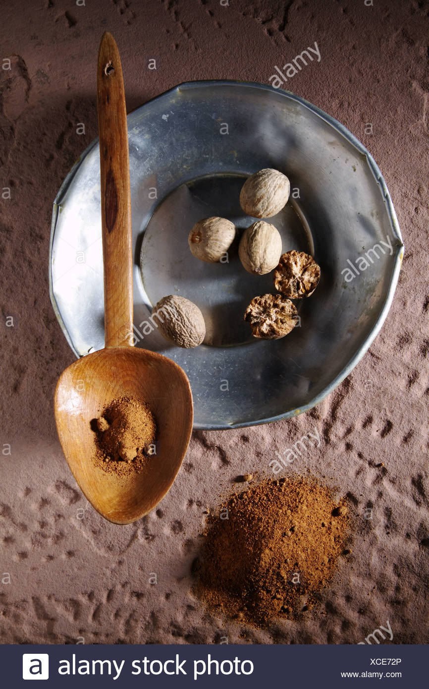 Nutmegs (Myristica fragrans), on a metal plate with a wooden spoon and ground nutmeg on a rustic stone base - Stock Image