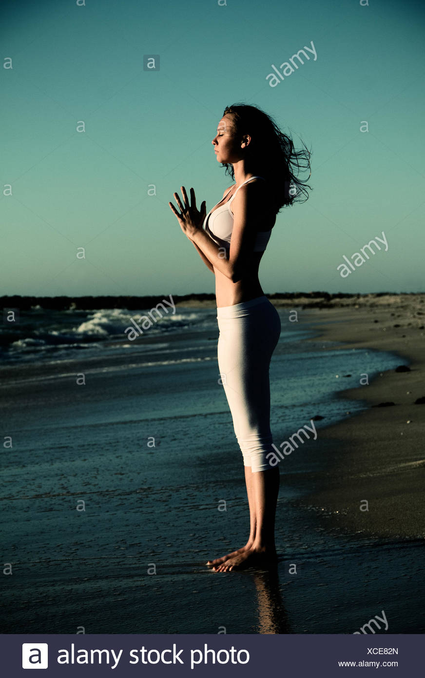 Side view of woman standing on beach doing yoga with hands in prayer position - Stock Image