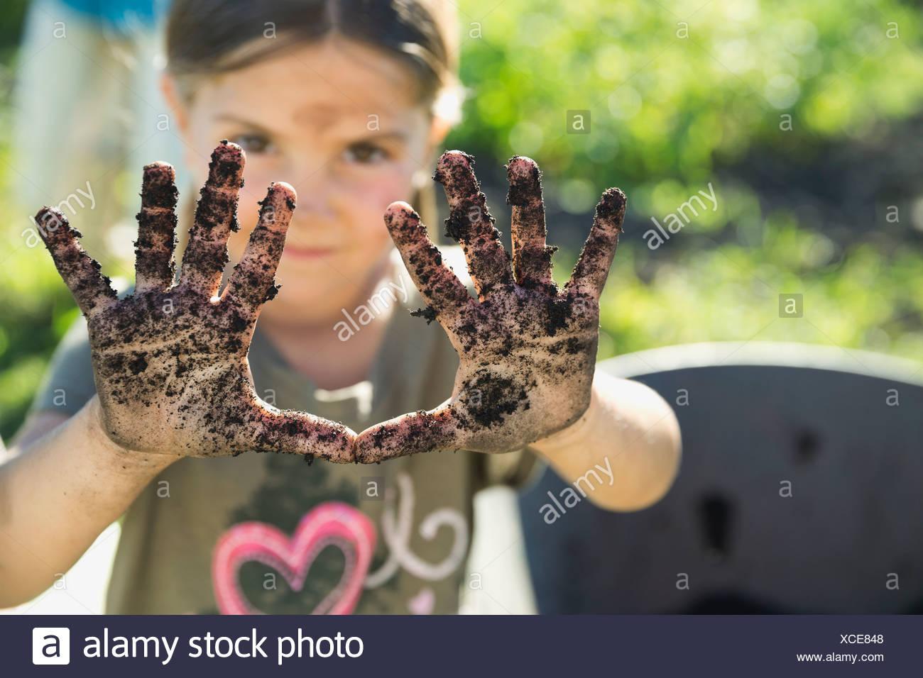Little girl showing hands full of garden dirt - Stock Image