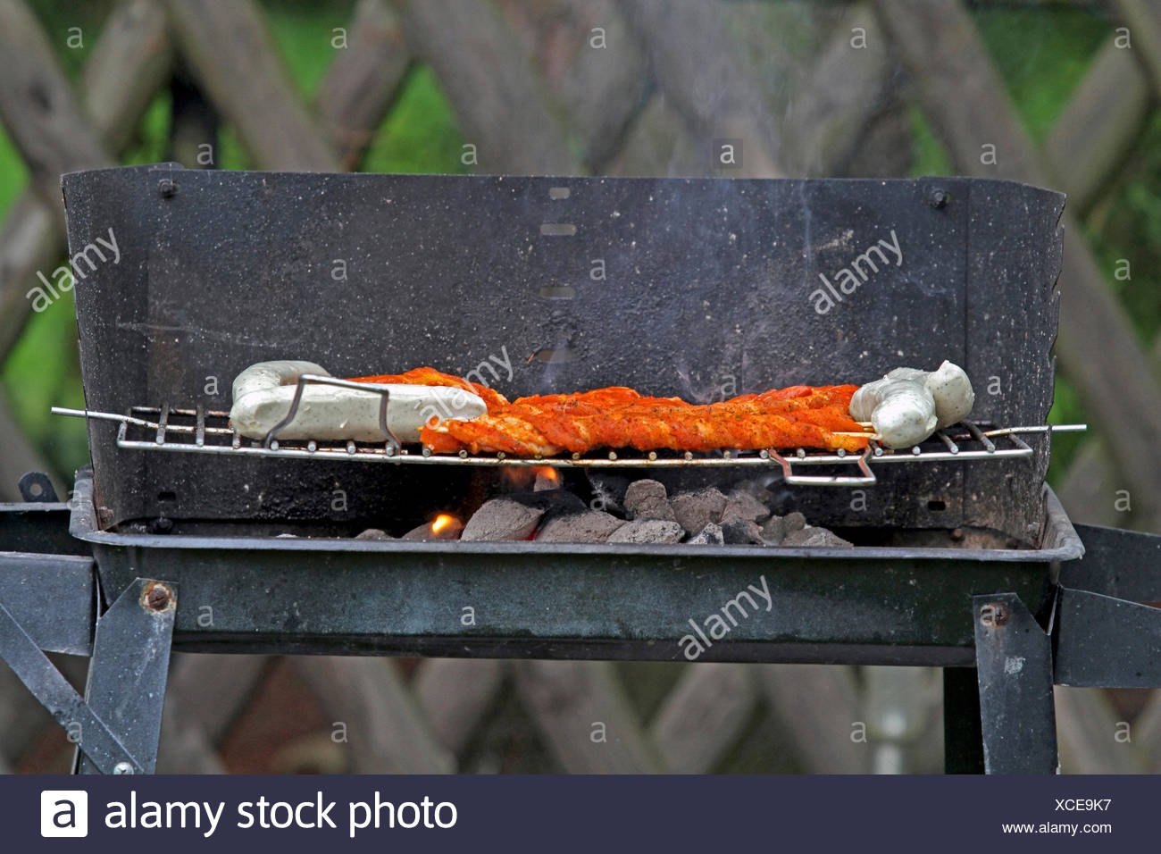 grill meat on a customary charcoal grill, Germany - Stock Image